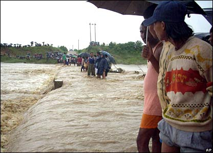 Villagers watch flooded paddy field in Nepal