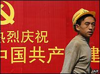Construction worker walks past Communist Party poster in Beijing - 19/10/2007