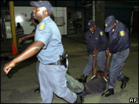 Police officers carry a man as they conduct a raid on the Central Methodist Church in Johannesburg, 31 January 2008