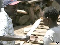 A member of the Kikuyu Mungiki gang threatens a man with a machete in Nairobi's Kibera slum, 10 January 2008