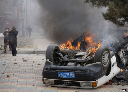 A burning car sits on a street in the Tibetan capital Lhasa