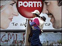 Una ecuatoriana con su hijo camina frente a un cartel de publicidad en Quito
