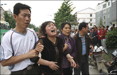 Parents grieve after identifying their child at a destroyed school in Dujiangyan on Thursday