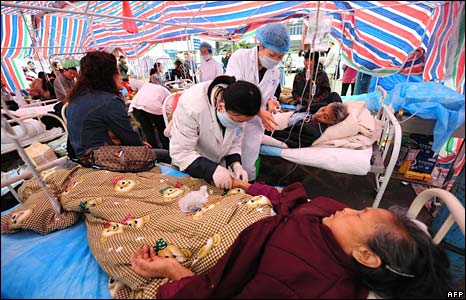 Injured earthquake victims receive treatment from medical personnel at a makeshift hospital in Dujiangyan on Thursday