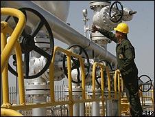 Worker checks over oil pumps in Iran
