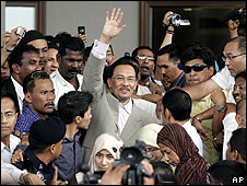 Malaysian opposition leader Anwar Ibrahim waves as he leaves court