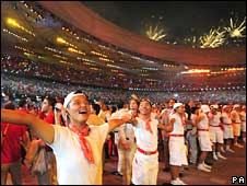 Volunteers enjoy the spectacular opening ceremony of the Beijing Olympics on Friday