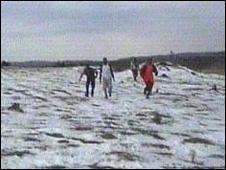Villagers walking across white fields