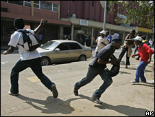 Union and anti-government protesters hurl stones at police during a rally in Manzini, Swaziland, 3 September 2008
