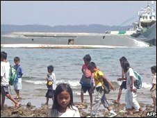 Children walk by the shore in view of the hull of the capsized wooden inter-island ferry beside another ferry in Masbate island in the Philippines