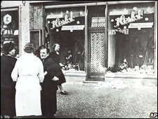 People stand outside a Jewish-owned shop attacked on Kristallnacht (November 1938)