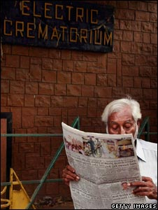 A man reads a newspaper outside the Chandanwadi Crematorium in Mumbai on Sunday, November 30