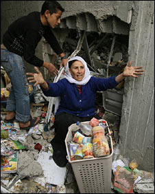 Two Palestinians recover belongings and food from their damaged house in Jabaliya on 29 December 2008