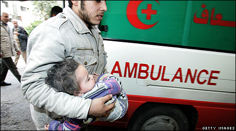 A Palestinian man carries an injured child into al-Shifa hospital 8 January 2009