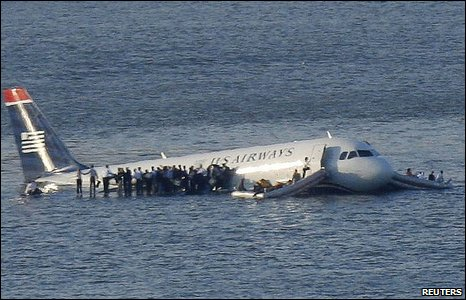 Passengers stand on the wing of the ditched airliner