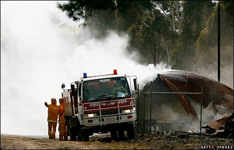 Firefighters hose a burnt shed at the Yarra Glen railway station, Victoria