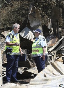 Police stand amid debris in Kinglake, Victoria, Australia.