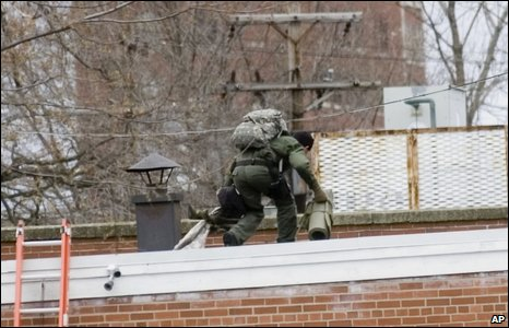 A sniper crosses a roof near the American Civic Association in downtown Binghamton
