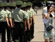 A woman takes a picture as Chinese paramilitary policemen march past on Tiananmen Square on June 3, 2009.