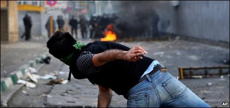 A protester throws an object towards police in Tehran, 20 June 2009