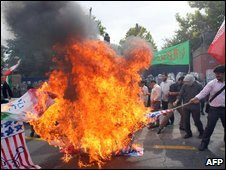 Iranian hardline students burn US and British flags during a protest outside the British embassy in Tehran on 23 June 2009