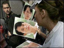 A supporter of Aung San Suu Kyi hands out photos of her during a protest in Paris after the court verdict.