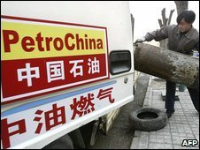 A Chinese man loads LPG canisters into a PetroChina vehicle