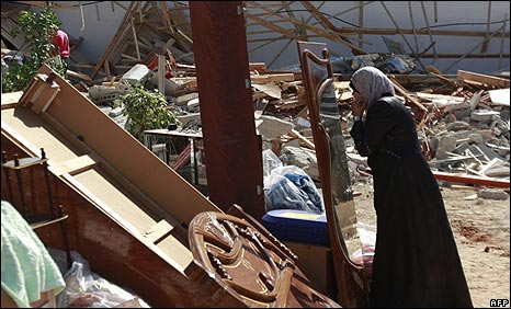 Palestinian women checks her reflection in a wardrobe door salvaged from demolished house in Beit Hanina