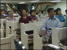 Migrant workers at health clinc worship service