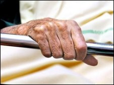 Patient's hand holding the bed rail