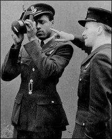 Une image en noir et blanc de John Henry Smythe regardant à travers une caméra.