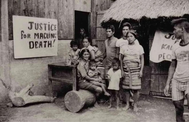SAMUN, (seated, with child on lap), wife of Macli-ing Dulag, and her children put up streamers in their house in the village of Bugnay in Tinglayan to call for justice over the murder of the Kalinga elder. MA. CERES DOYO