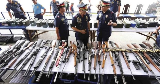"""Fifty-six  rifles, 18 pistols, 27 hand grenades, 62 rifle grenades and over 17,000 rounds of ammunition were found inside a """"secret room"""" at  36 Tandang Sora Ave., according to police. —EDWIN BACASMAS"""