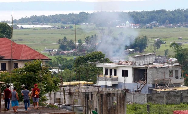 Residents watch a house that caught fire when the government troops continue to battle with Muslim militants who lay siege in Marawi city in southern Philippines Thursday, May 25, 2017. Army tanks packed with soldiers rolled into the southern Philippine city Thursday to try to restore control after ISIS-linked militants launched a violent siege that sent thousands of people fleeing for their lives and raised fears of extremists gaining traction in the country. (AP Photo/Bullit Marquez)