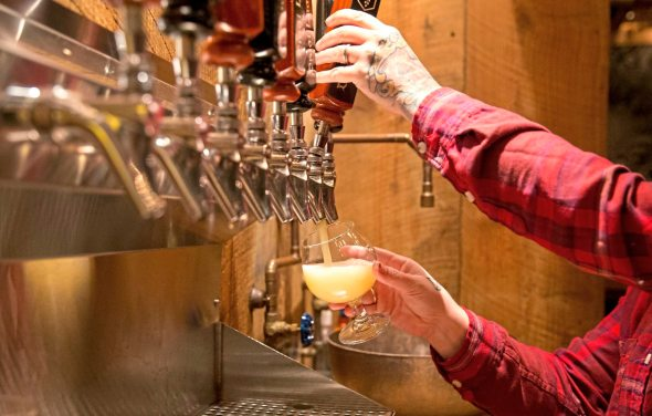 Santana Woodring, taproom manager and resident artist, pours a glass of cake beer at the Draai Laag Brewing Co. in Millvale, which in March is being rebranded as Strange Roots Experimental Ales. (Antonella Crescimbeni/Post-Gazette)