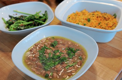 Counterclockwise: Pinto beans, carrot farofa and sauteed spinach prepared by Keyla Nogueira Cook in the kitchen of Navus House on the North Side Tuesday, April 24, 2018 in Pittsburgh. (Pam Panchak/Post-Gazette)