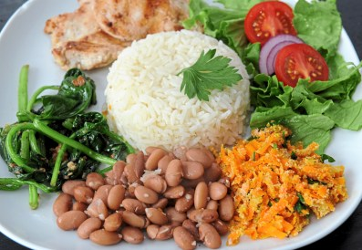 A Prato Feito or a Brazilian Blue Plate Special with pinto beans, carrot farofa, lettuce and tomato salad, pan-seared chicken breast, sauteed spinach and rice prepared by Keyla Nogueira Cook in the kitchen of Navus House on the North Side Tuesday, April 24, 2018 in Pittsburgh. (Pam Panchak/Post-Gazette)