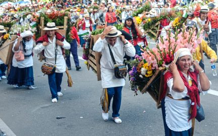 """Flower farmers carry elaborate flower arrangements on wooden """"silletas"""" Monday Aug. 7, 2017, during the 60th anniversary of the flower festival in Medellin, Colombia. (Nate Guidry/Post-Gazette)"""