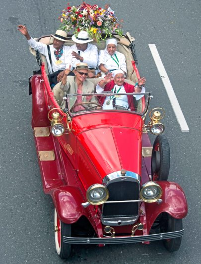 Passengers in an antique vehicle wave to the crowd Monday Aug. 7, 2017, during the 60th anniversary of the flower festival in Medellin, Colombia. (Nate Guidry/Post-Gazette)