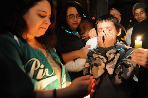 Eric Callender, 12, center, covers his face as he speaks about his best friend David McIntyre, 11, during a candlelight vigil on Hays Avenue in Mt. Oliver on Tuesday, December 1, 2015. David was shot and killed and his brother CJ Mikula-Conrad, 16, was critically injured when a gunman enter their home and began shooting one month ago. Angela Mancini-Boyer, left, of McKees Rocks bows her head as Miranda Malloy, 16,second from left, hugs Alayzia Cain, 10. Rebecca Droke/Post-Gazette