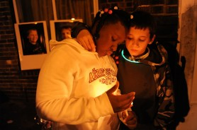 Alayzia Cain, 10, and Eric Callender, 12, both of Mt. Oliver comfort each other as they gather for a candlelight vigil in honor of David McIntyre, 11, on Hays Avenue in Mt. Oliver on Tuesday, December 1, 2015. David was shot and killed and his brother CJ Mikula-Conrad, 16, was critically injured when a gunman enter their home and began shooting one month ago. Cain and Callender were best friends of David. Rebecca Droke/Post-Gazette