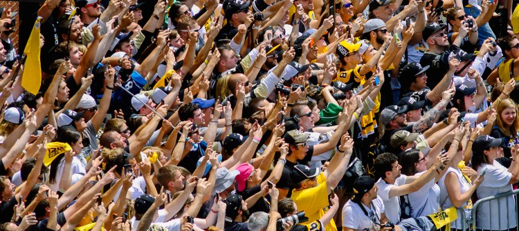 A mass of fans shooting cell phone pictures of the cup on the boulevard. (Darrell Sapp/Post-Gazette)