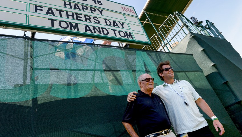 Tom M. Day, of Las Vegas, poses with his son, Tom F. Day, of West Hampton Beach, NY, on hole 16 early Sunday as workers have fun with the boards before start of play for the final round. (Matt Freed/Post-Gazette)