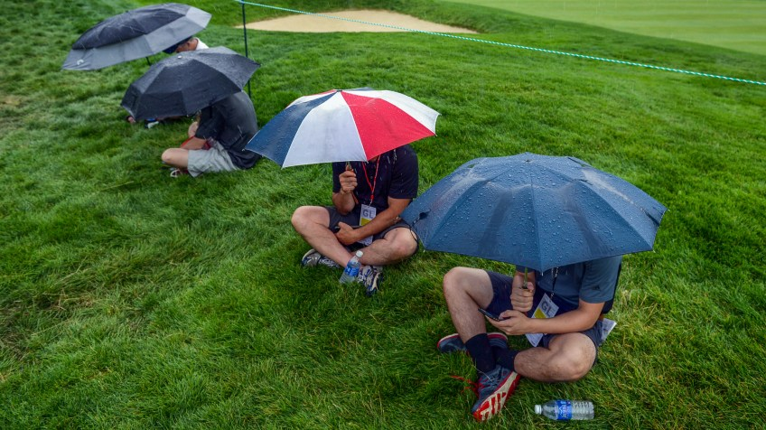 Spectators wait for the rain to stop and for play to resume on the 16th hole. (Steve Mellon/Post-Gazette)