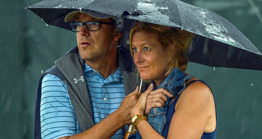 Andy and Ashley Staples of Phoenix, Az, wait out a rain delay on the 17th hole. (Steve Mellon/Post-Gazette)