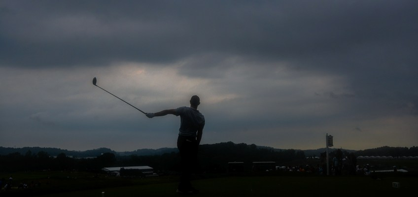 Rory McIlroy watches after teeing off on the 12th hole as clouds loom in the background on Thursday. (Lake Fong/Post-Gazette)