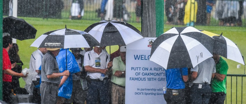 Spectators huddle uner the Epic Putt entrance in Spectator Square Thursday during the first round. (Matt Freed/Post-Gazette)