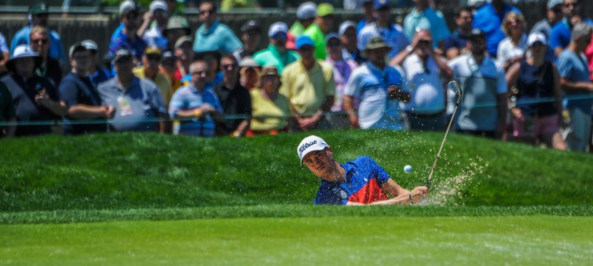 Justin Thomas hits onto the green at the eighth hole on Friday. (Rebecca Droke/Post-Gazette)