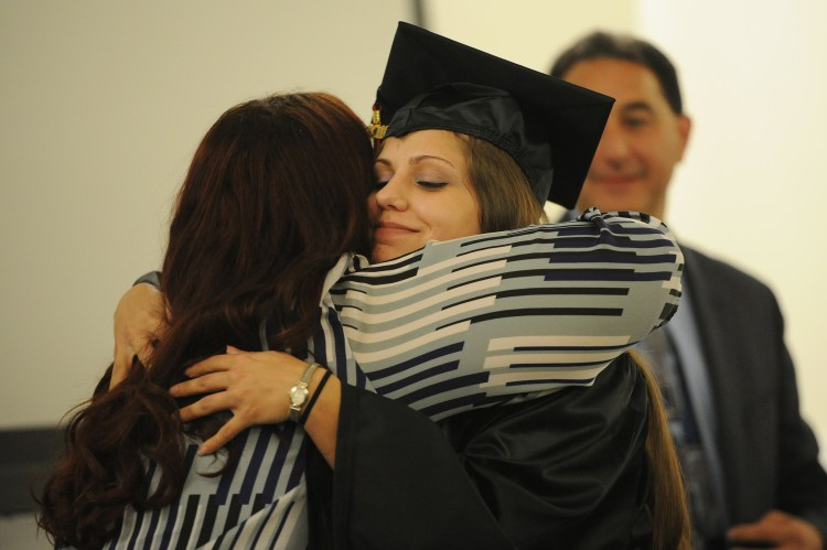 Michelle Suriano, former director of finance at ITT Technical Institute hugs graduate Jordan Wiegmann of Burgettstown during a ceremony at Pittsburgh Technical Colleges in Oakdale Wednesday, October 12, 2016.