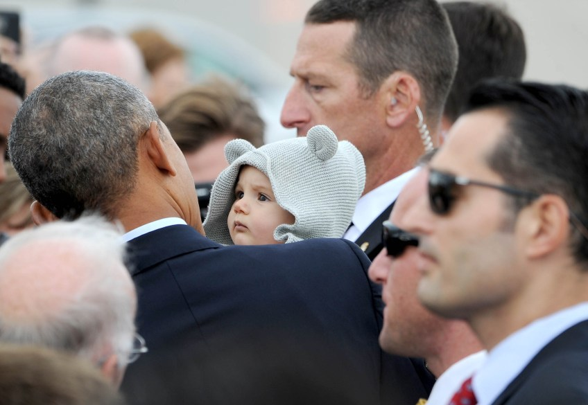 President Barack Obama holds a baby as he greets invited guests after landing at the 171st Air Refueling Wing in Coraopolis. (Photo by Michael Henninger/Post-Gazette)